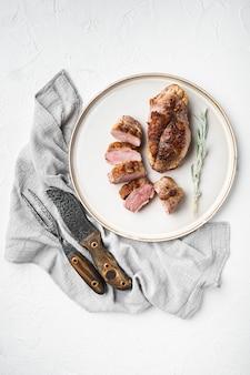 白い石の上面図のプレートにおいしいスライスしたロースト鴨胸肉