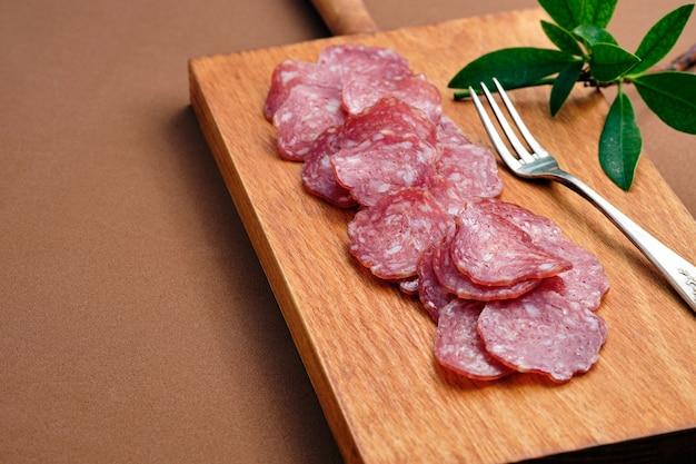 Вкусные ломтики испанской иберийской колбасы на разделочной доске