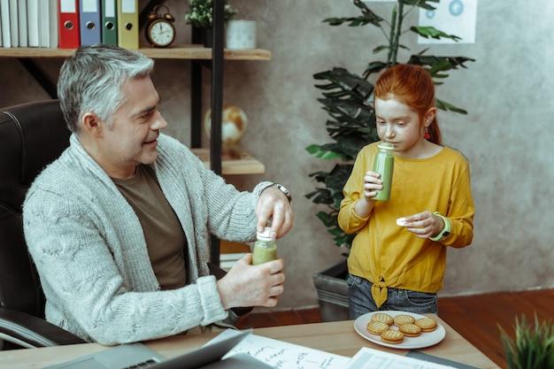 Вкусный запах. симпатичная рыжая девушка держит бутылку со смузи, нюхая его