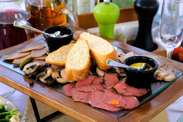 Delicious smoked cutted bacon on a wooden tray on a banquet table in a luxury restaurant.
