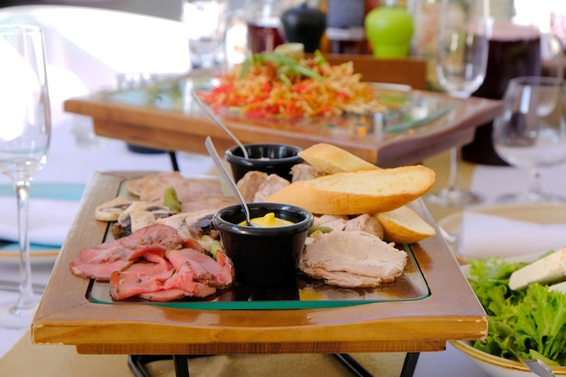 Delicious smoked cutted bacon on a wooden tray on a banquet table in a luxury restaurant