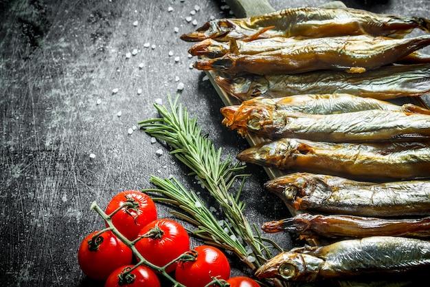Вкусная копченая рыба с розмарином и помидорами на ветке на деревенском столе