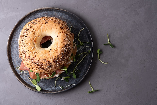 Delicious snack concept, bagel with cream cheese, dry cured ham and microgreens on a plate on a gray background.