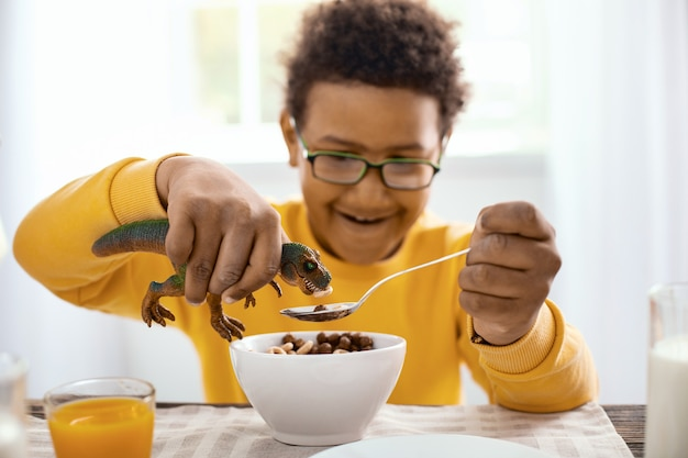 Delicious snack. pleasant pre-teen boy eating cereals for breakfast and feeding them to his toy dinosaur while smiling