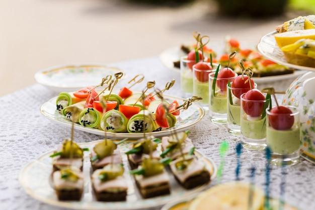 Вкусные закуски на свадебном столе в роскошном ресторане на открытом воздухе