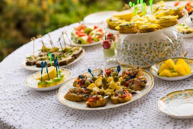 Delicious snacks on wedding reception table in luxury outdoor restaurant