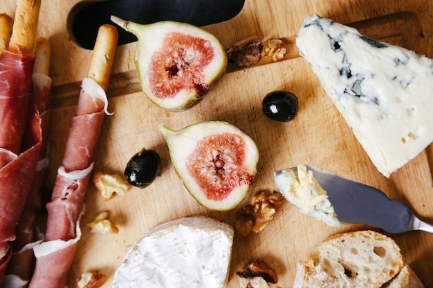Delicious snacks on wooden board