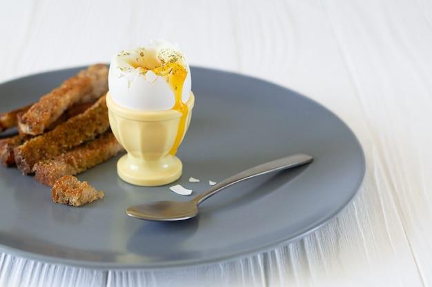 朝食にトーストしたパンが入ったエッグカップに入ったおいしい半熟卵