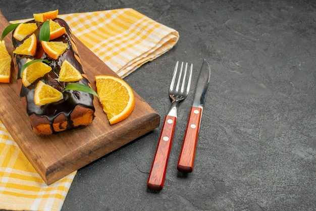 Delicious soft cakes on board and cut oranges with leaves on green striped towel of the dark table