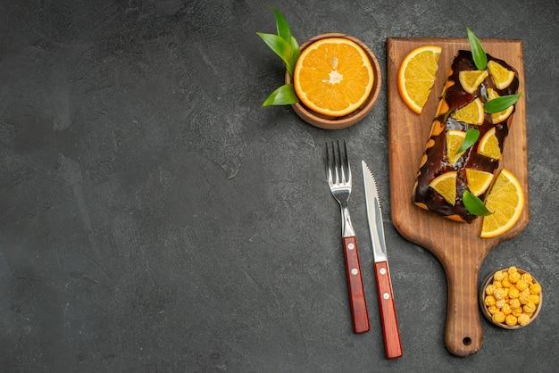 おいしいソフトケーキを乗せて、暗いテーブルの葉でオレンジをカットします