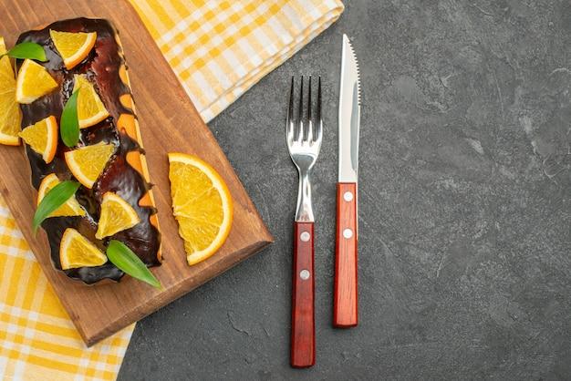 木の板においしいソフトケーキと緑の縞模様のタオルに葉でレモンをカット