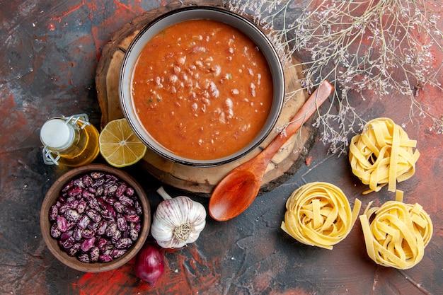 Deliziosa zuppa per cena con un cucchiaio e limone su un vassoio di legno fagioli aglio cipolla e altri prodotti sulla tabella di colori misti