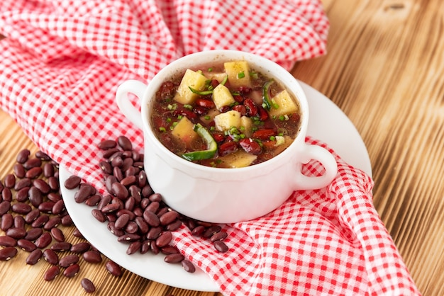 Delicious soup of fresh red beans with the addition of meat, potatoes and herbs on a wooden background.
