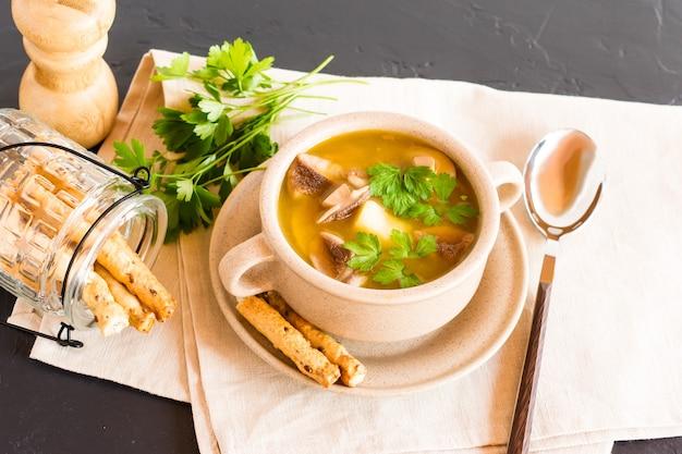 新鮮な森のきのこのおいしいスープとハーブとスパイスをボウルに入れてスープにします。布ナプキンに。ダイエット食品。