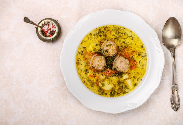 Delicious soup with chicken or turkey meatballs with vegetables - potatoes, carrots, dill, parsley