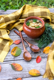 Delicious soup with croutons in a clay pot with herbs on a wooden table.