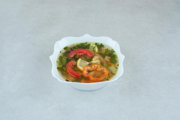 Вкусный суп с зеленью и перцем в белой тарелке.