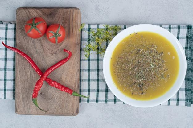 Вкусный суп с зеленью и двумя помидорами, двумя острыми перцами на деревянной доске.