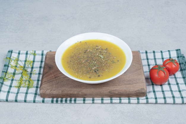 Delicious soup with greens and two tomatoes on tablecloth