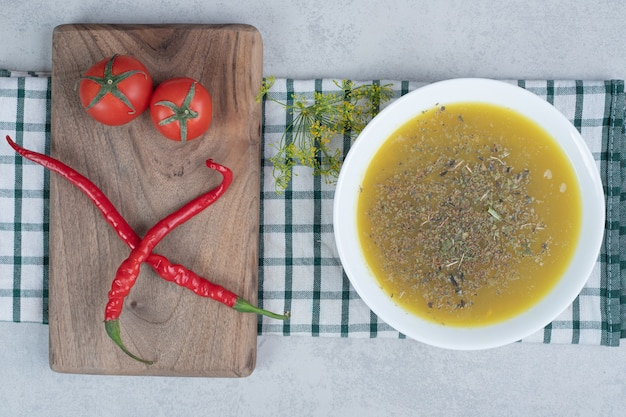 Delicious soup with greens and two tomatoes, two hot pepper on wooden board.
