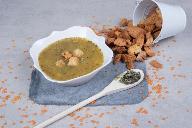 テーブルクロスにレンズ豆とスプーンを添えたおいしいスープ 無料写真