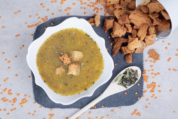 Deliziosa zuppa con lenticchie e cucchiaio sulla tovaglia