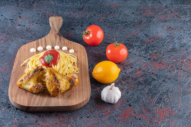 야채와 함께 나무 보드에 맛 있는 스파게티와 닭 날개.