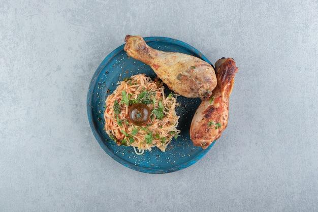 青いプレートに美味しいスパゲッティとグリルチキン