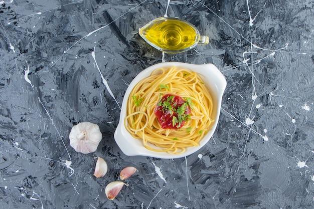 토마토 소스와 올리브 오일을 곁들인 하얀 접시에 맛있는 스파게티.