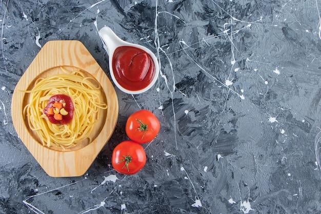 Вкусные спагетти на деревянной тарелке со свежими помидорами и кетчупом.