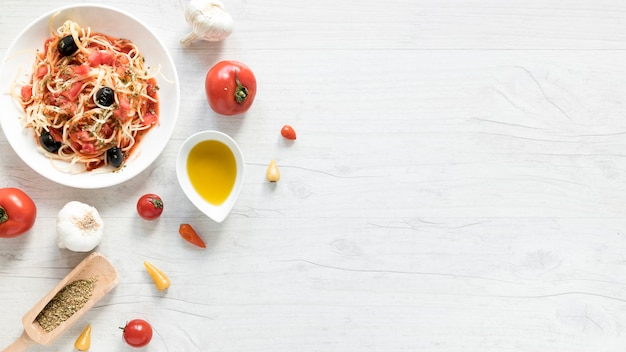 Delicious spaghetti pasta on plate; fresh tomato; bowl of olive oil and herbs on wooden desk