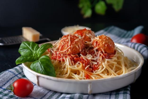 ミートボール、パルメザン チーズ、トマト ソースのおいしいスパゲッティ パスタ プレートにキッチン クロスの上