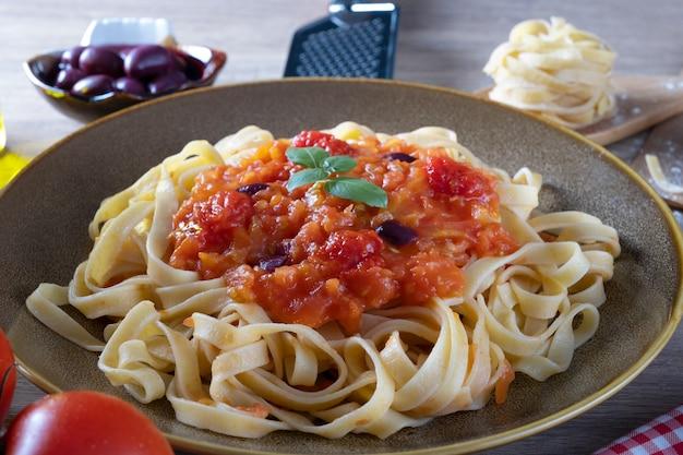 Delicious spaghetti of tagliatelle with tomato sauce, selective focus.