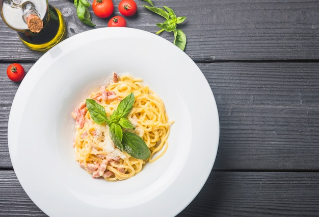 Delicious spaghetti in a white plate with olive oil; tomatoes and basil leaves on wooden table