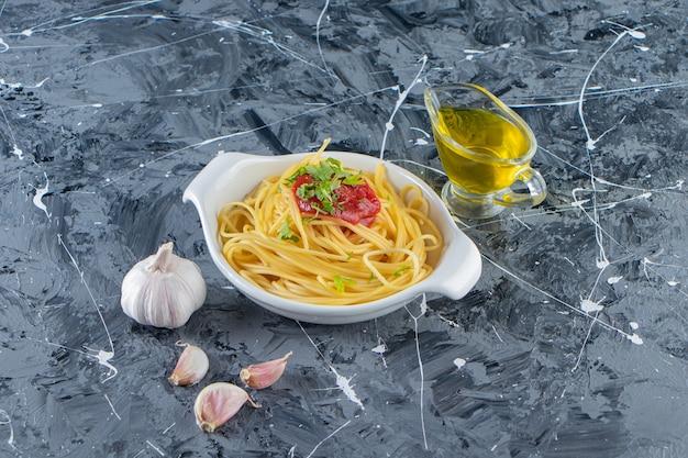 Deliziosi spaghetti sul piatto bianco con salsa di pomodoro e olio d'oliva.