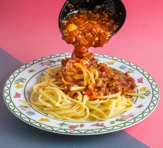 ボロネーゼソースのおいしいスパゲッティを白い正方形のプレートで提供しています