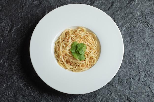 白い皿にグリーンが入った美味しいスパゲッティ。
