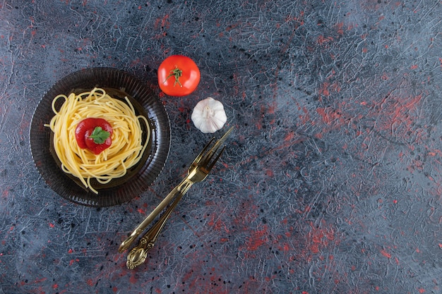 Вкусные спагетти с томатным соусом на черной тарелке со столовыми приборами.