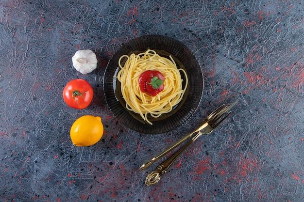 칼 붙이와 검은 접시에 토마토 소스와 함께 맛 있는 스파게티.
