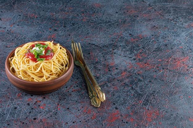 칼 붙이와 나무 그릇에 토마토 소스와 함께 맛 있는 스파게티.