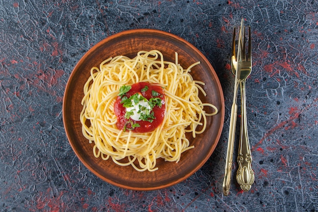 칼 붙이와 나무 접시에 토마토 소스와 함께 맛 있는 스파게티.