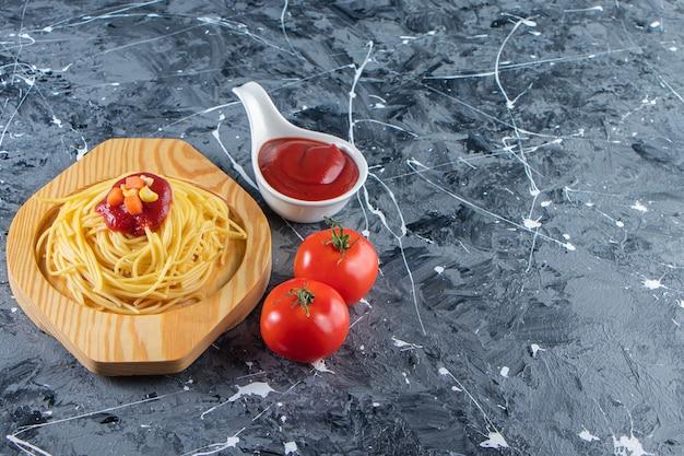 Deliziosi spaghetti sul piatto di legno con pomodori freschi e ketchup.