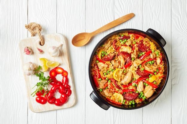 흰색 나무 테이블에 검은 접시에 발렌시아 봄바 쌀, 닭 허벅지 고기, 초리 조 소시지, 야채와 향신료가 들어간 맛있는 스페인 치킨 빠에야, 평평한 누워