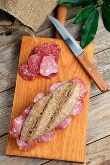 Вкусный сэндвич с испанской иберийской колбасой на разделочной доске