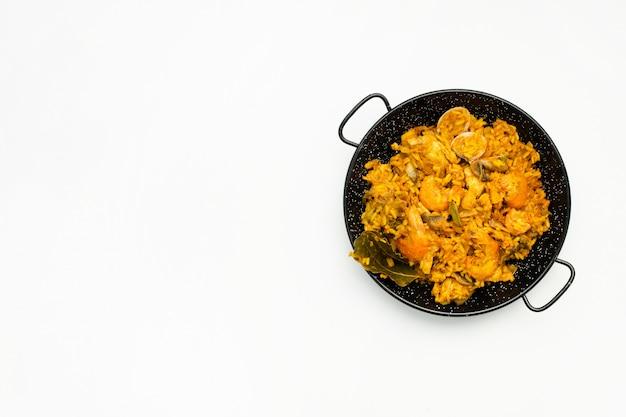 Вкусный испанский рис в сковороде паэлья на белом фоне