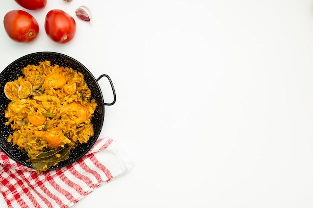 Delizioso riso spagnolo in una padella per paella su sfondo bianco