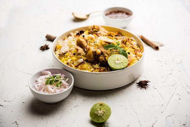 不機嫌そうな背景の上にボウルに入れられたおいしいスパイシーなチキンビリヤニ、それは人気のあるインド料理とパキスタン料理です