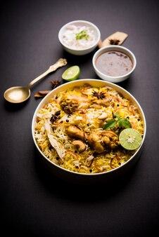 변덕스러운 배경 위에 그릇에 담긴 맛있는 매운 치킨 비리야니, 인기 있는 인도 및 파키스탄 음식