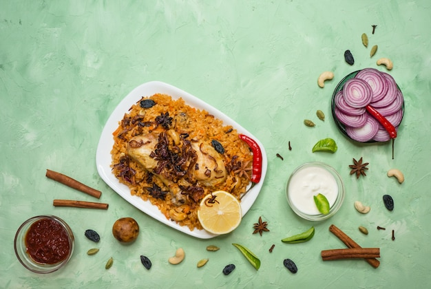 Delicious spicy chicken biryani in white bowl on green background, indian or pakistani food.