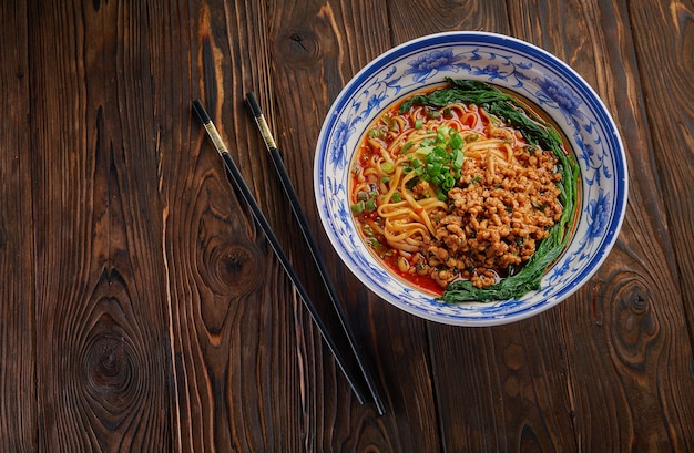 Delicious and spicy homemade sichuan rice noodle in traditional blue bowl with black chopsticks on wooden table, asian food concept copy space for menu design